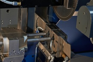 Close-up of twin cutting head; machine cuts two workpieces simultaneously
